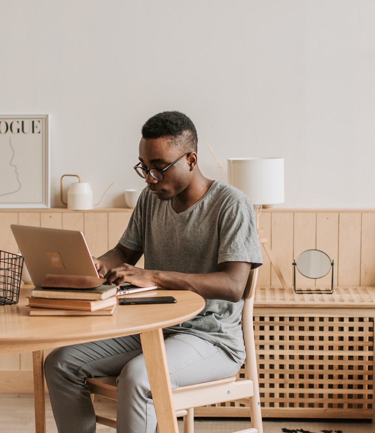 man at desk with laptop and books